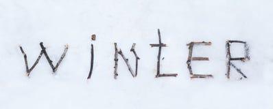 El invierno de la palabra escrito con los palillos de madera quebrados en backgr de la nieve Imagen de archivo libre de regalías