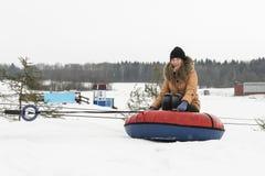 El invierno, el ocio, el deporte y la gente un concepto - la muchacha feliz o la mujer, sube en el tubo de la nieve el elevador Fotos de archivo