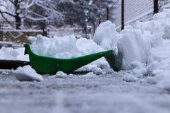 El invierno está ganando fuerza Un hombre con la pala plástica que traspala nieve de las calzadas del hogar Todavía nevando y nev fotografía de archivo