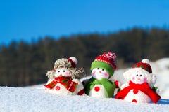 El invierno, la Navidad - tres muñecos de nieve felices se colocan contra la perspectiva del cielo azul Imágenes de archivo libres de regalías
