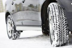 El invierno pone un neumático las ruedas instaladas en el coche del suv al aire libre Imágenes de archivo libres de regalías