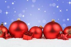 El invierno rojo de la nieve de la decoración de las bolas de la Navidad protagoniza la copia del fondo Imágenes de archivo libres de regalías