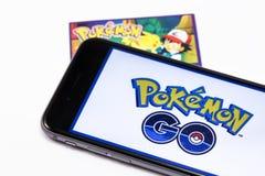 El iPhone negro 6s y Pokemon de Apple de la marca va en la pantalla Pokemo Fotografía de archivo libre de regalías