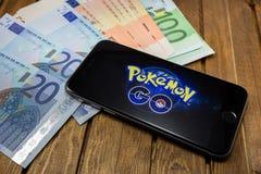 El iPhone 6s de Apple con Pokemon va en la pantalla Imágenes de archivo libres de regalías