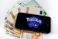 El iPhone 6s y Pokemon de Apple va fondo en la pantalla Imagenes de archivo