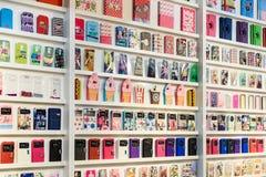 El iPhone y Samsung coloridos llaman por teléfono a los casos para la venta en tiendas de los teléfonos móviles foto de archivo libre de regalías