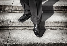 Piernas del hombre de negocios que toman a paso en un nivel inferior en las escaleras Imagenes de archivo