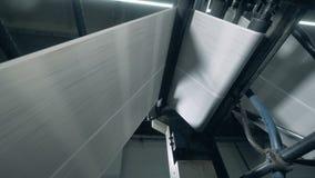 El ir de papel en un transportador rodante en la imprenta almacen de video