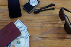 El ir en viaje de las vacaciones, en la tabla es un pasaporte con los dólares del dinero Foto de archivo