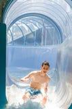 El ir feliz del hombre del adolescente abajo en un tobogán acuático Fotos de archivo libres de regalías