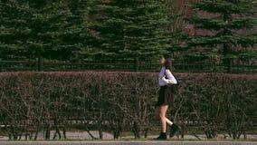 El ir femenino abajo de la calle después de clases de escuela La muchacha asiática va a casa con un bolso almacen de metraje de vídeo