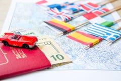 El ir a viajar Pasaporte, lupa, coche rojo del juguete y dinero en mapa Ahorre el dinero en el viaje, planeando para el concepto  Fotografía de archivo libre de regalías