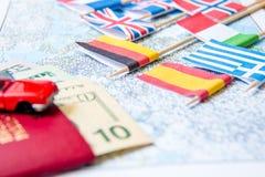 El ir a viajar Pasaporte, lupa, coche rojo del juguete y dinero en mapa Ahorre el dinero en el viaje, planeando para el concepto  Foto de archivo