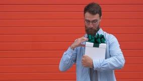 El júbilo barbudo del hombre para conseguir la caja de regalo blanca con el arco verde de hembra entrega la pared roja metrajes