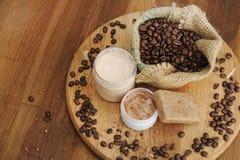 El jabón, crema y friega y los granos de café en saco de la arpillera fotografía de archivo