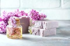 El jabón hecho a mano, el tarro de cristal con aceite fragante y la lila florece para el balneario y el aromatherapy Fotografía de archivo