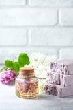 El jabón hecho a mano, el tarro de cristal con aceite fragante y la lila florece para el balneario y el aromatherapy Foto de archivo libre de regalías