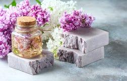 El jabón hecho a mano, el tarro de cristal con aceite fragante y la lila florece para el balneario y el aromatherapy Fotografía de archivo libre de regalías