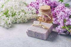 El jabón hecho a mano, el tarro de cristal con aceite fragante y la lila florece para el balneario y el aromatherapy Imagen de archivo libre de regalías