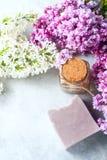 El jabón hecho a mano, el tarro de cristal con aceite fragante y la lila florece para el balneario y el aromatherapy Imagen de archivo