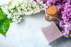 El jabón hecho a mano, el tarro de cristal con aceite fragante y la lila florece para el balneario y el aromatherapy Imágenes de archivo libres de regalías
