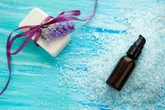 El jabón orgánico natural embotella el aceite esencial y la sal en una tabla de madera azul, balneario del mar Foto de archivo libre de regalías