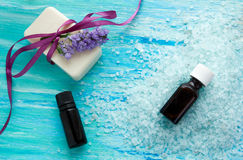 El jabón orgánico natural embotella el aceite esencial y la sal en una tabla de madera azul, balneario del mar Fotografía de archivo
