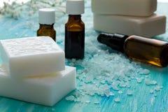 El jabón orgánico natural embotella el aceite esencial y la sal en una tabla de madera azul, balneario del mar Imagen de archivo