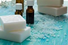 El jabón orgánico natural embotella el aceite esencial y la sal en una tabla de madera azul, balneario del mar Imagen de archivo libre de regalías