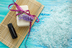 El jabón orgánico natural embotella el aceite esencial y la sal en una tabla de madera azul, balneario del mar con Fotos de archivo
