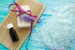 El jabón orgánico natural embotella el aceite esencial y la sal en una tabla de madera azul, balneario del mar con las flores Imagenes de archivo