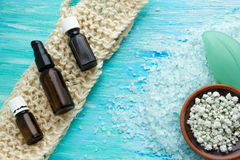 El jabón orgánico natural embotella el baño herbario del aceite esencial y de la sal del mar en una tabla de madera azul, con las Foto de archivo libre de regalías
