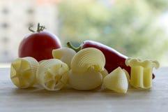 El jalapeno rojo madurado, el tomate rojo y la diversa mezcla de pastas en la tabla de madera, alistan para cocinar Imagenes de archivo