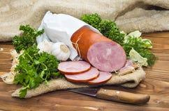 El jamón cortó la salchicha de cerdo con ajo y la hierba Fotografía de archivo libre de regalías