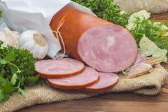 El jamón cortó la salchicha de cerdo con ajo y la hierba Fotos de archivo libres de regalías