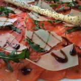 El jamón de Parma de la pizza con el queso parmesano de la rebanada herbario y la espinaca en restaurante, adorna con la barra de Foto de archivo