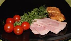 El jamón, los tomates de cereza y los verdes cortados sirvieron en la placa negra Foto de archivo