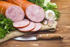 El jamón cortó la salchicha de cerdo con ajo y la hierba Imágenes de archivo libres de regalías