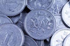 El japonés un yen acuña en un fondo negro Imagen de archivo