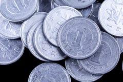 El japonés un yen acuña en un fondo negro Fotos de archivo