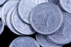 El japonés un yen acuña en un fondo negro Imagenes de archivo