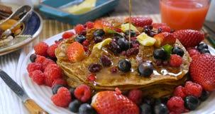 El jarabe de arce de colada sobre un desayuno de crepes con las bayas y seca las frutas almacen de video