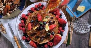 El jarabe de arce de colada sobre un desayuno de crepes con las bayas y seca las frutas almacen de metraje de vídeo