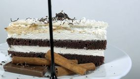 El jarabe de chocolate vierte en una rebanada de torta, cámara lenta en 1000fps, girando metrajes