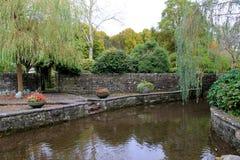 El jardín bonito de las paredes de piedra, hombre hizo la charca, las flores y los árboles Fotos de archivo