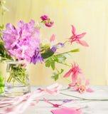 El jardín florece en el florero de cristal en la tabla de madera Imagen de archivo libre de regalías