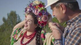 El jardinero adulto en un casco y guardapolvos camina para arriba a una muchacha regordeta linda con una guirnalda en su cabeza S almacen de video