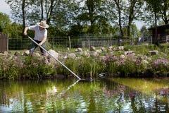 El jardinero con el sombrero de paja limpia la charca Imagen de archivo