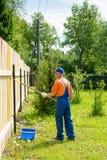 El jardinero en uniforme del azul pinta la nueva cerca de madera Foto de archivo libre de regalías
