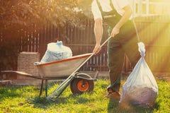 El jardinero limpia las hojas en la yarda Al lado de él es un carro con estiércol vegetal que el sol brilla brillantemente fotos de archivo